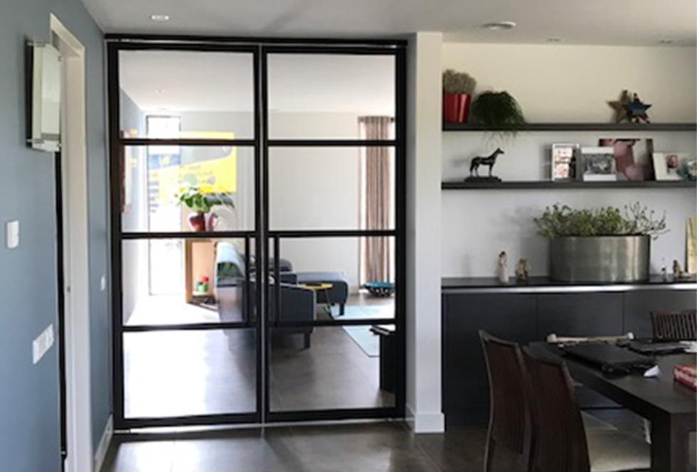 Huiskamer met dubelle stalen binnendeuren: stalen taatsdeuren, stalen schuifdeuren of stalen scharnierdeuren