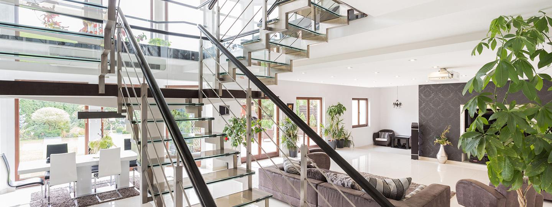 Moderne woonkamer met stijlvolle rvs trap met glazen trap en bordes met balustrade