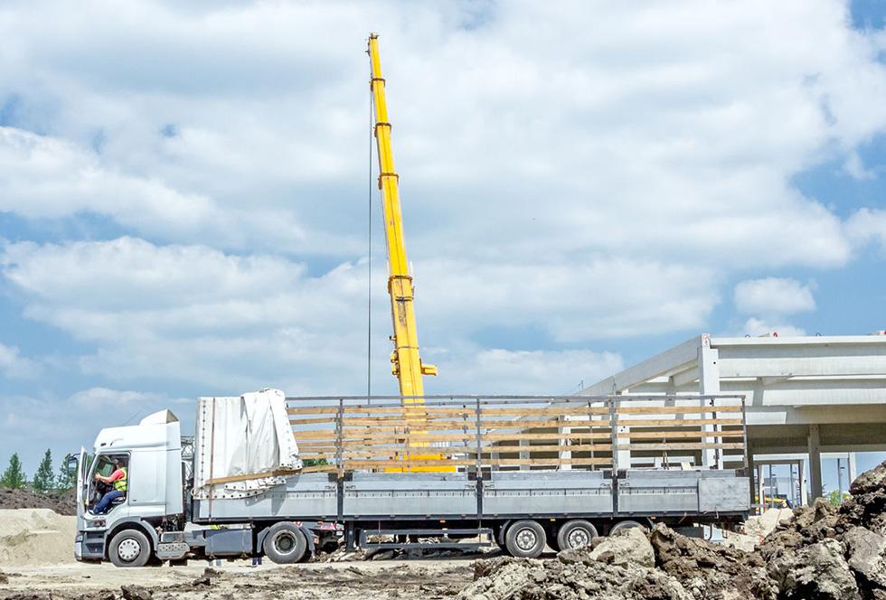 Mobiele kraan tilt een stalen constructiebalk uit een vrachtwagen bij de bouw van een bedrijfshal