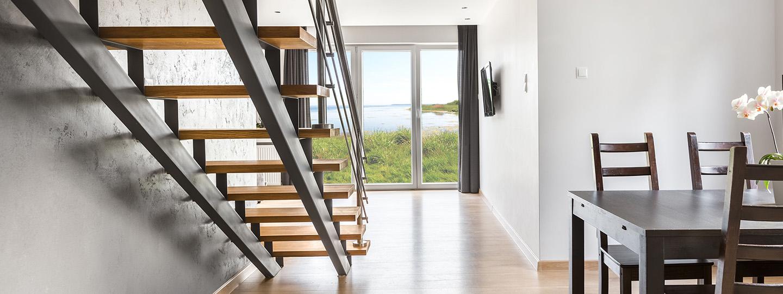 Robuuste rechte trap met 2 stalen trapbomen stalen balustrade en houten traptreden gezien vanaf achterkant
