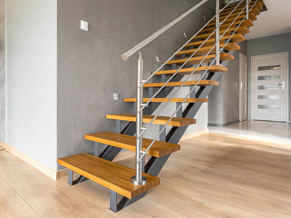 Robuuste rechte trap met 2 stalen trapbomen stalen balustrade en houten traptreden gezien vanaf voorkant