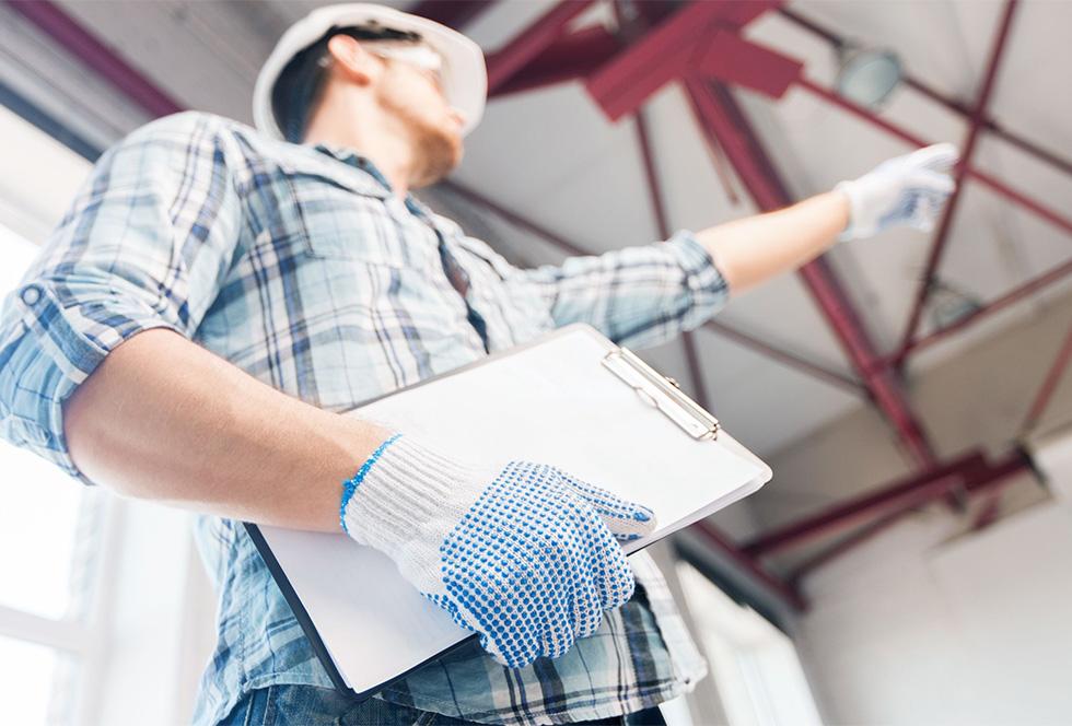 Aannemer wijst naar een stalen dakconstructie van een bedrijfshal