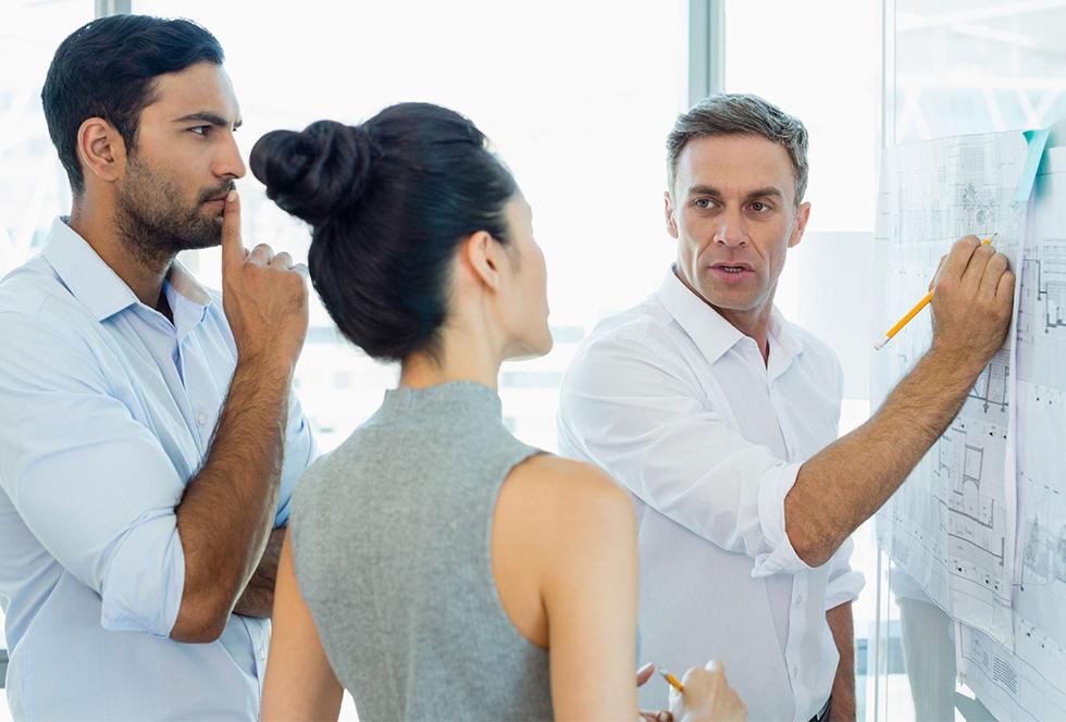 Architecten die een ontwerp van een gebouw bespreken met een stalen constructie op een whiteboard