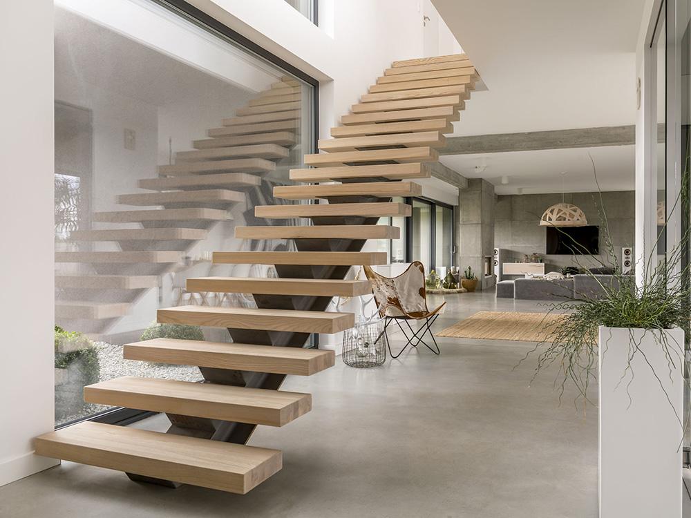 Stijlvolle stalen trap met een enkele trapboom en met dikke houten traptreden